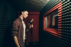 Emotional handsome singer with microphone singing song at sound recording studio. Side view photo. copy space. interest stock image