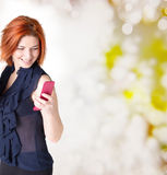 Emotional happy woman with red hair and a telephone Royalty Free Stock Photo