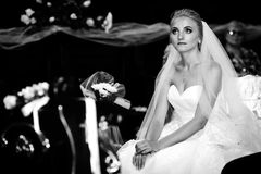 Emotional innocent bride posing at wedding ceremony in church b& Stock Photo