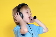 The emotional kid in ear-phones Royalty Free Stock Photos