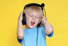 The emotional kid in ear-phones. On a yellow background Royalty Free Stock Image