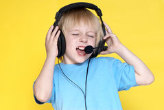 The emotional kid in ear-phones Stock Images