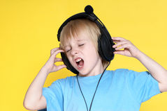 The emotional kid in ear-phones Royalty Free Stock Photography