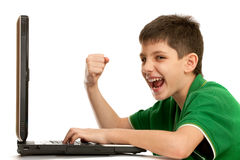 Emotional kid is playing computer game Stock Images