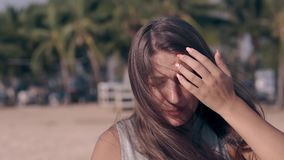 Emotional lady talks and shakes long dark hair close view. Emotional lady talks and shakes long dark hair intensively against green blurred palms close view stock video