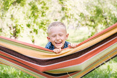 Emotional little boy in hammock in summer garden Stock Photos