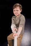 Emotional little boy pulling rope. Isolated on black royalty free stock photography