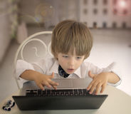 Emotional little boy using laptop Stock Image