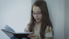 Emotional little girl with glasses writes in his diary at window.