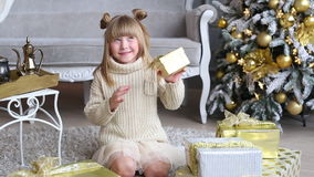 Emotional little girl holds a gift box in hands, try to open near Christmas tree at home stock footage