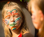 Emotional little girl with paint on his face looks in the mirror. Royalty Free Stock Photography