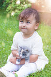 Emotional little girl playing with a cat in the park stock photography