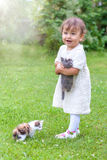 Emotional little girl playing with a cat in the park royalty free stock image