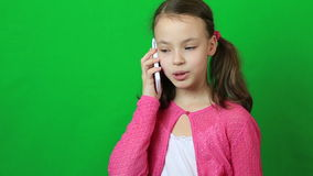 Emotional little girl talking on a smartphone stock video
