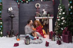 Two romantic people laughing while celebrating New Year near the fireplace royalty free stock images