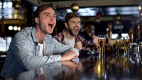Emotional male fans cheering for favorite team in pub, celebrating game victory. Stock photo stock photography