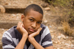 Emotional male teen. Sad African-American Male sitting in outdoor setting Royalty Free Stock Images