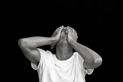 Emotional man. Cowering in grief against black background Royalty Free Stock Photography