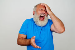Emotional man with beard holding his head with eyes screwed and Stock Photography