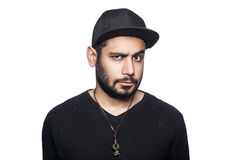 Emotional man with black t-shirt and cap. Portrait of young doubtful thinking man with black t-shirt and cap looking at camera with unsure eyes. studio shot Stock Photography