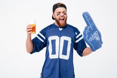Emotional man fan in blue t-shirt drinking beer. Image of handsome man fan in blue t-shirt wearing fan finger number one glove standing isolated over white Royalty Free Stock Photos