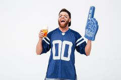 Emotional man fan in blue t-shirt drinking beer. Picture of emotional man fan in blue t-shirt wearing fan finger number one glove standing isolated over white Stock Images