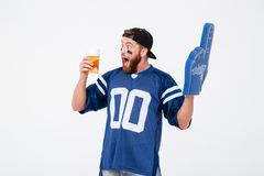 Emotional man fan in blue t-shirt drinking beer. Picture of emotional man fan in blue t-shirt wearing fan finger number one glove standing isolated over white Royalty Free Stock Images
