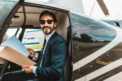 Emotional man feeling happy and holding his documents. Cheerful happy young businessman sitting in the helicopter cabin and smiling happily while holding stock photography