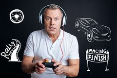 Emotional man feeling interested while playing video games stock images