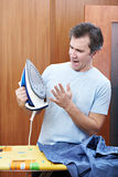 Emotional man with hot iron before ironing Royalty Free Stock Photography