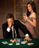 Emotional man loser in poker and ladies with glass of champagne Stock Images