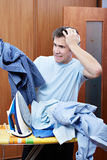 Emotional man with pile of laundry before ironing Stock Photo