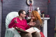 Emotional man sitting with newspaper and talking to his interested wife royalty free stock image