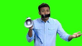 Emotional man with taped mouth can not speak. Chroma key background. Censorship concept stock footage