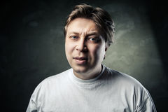 Emotional middle aged doubting man over gray Royalty Free Stock Photography