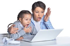 Emotional mother and daughter using laptop isolated on white background. Emotional mother and daughter using laptop posing against white royalty free stock photo
