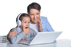 Emotional mother and daughter using laptop on white background. Emotional mother and daughter using laptop posing isolated on white background royalty free stock photo