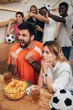 Emotional multicultural football fans pointing by fingers and watching soccer match at bar with chips and beer. Glasses stock images
