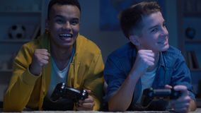 Emotional multiracial male friends winning computer game, leisure activity. Stock footage stock video