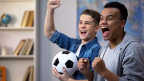 Emotional multiracial teenage friends cheering for national soccer team, fans