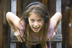 Emotional naughty little girl with headphones, close-up portrait Stock Photo