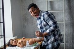Emotional nervous frightened dad is changing his baby diaper, close-up photo stock image