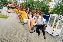 Emotional newlyweds screaming while riding on high carousel in amusement park. Expressive wedding couple at carnival. Stock Photography