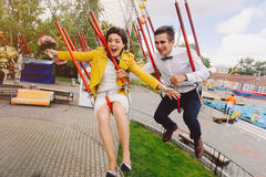 Emotional newlyweds screaming while riding on high carousel in amusement park. Expressive wedding couple at carnival. Royalty Free Stock Photos