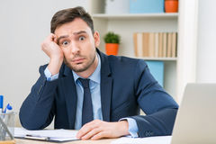 Emotional office worker sitting at the table royalty free stock photo