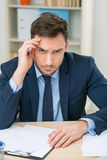Emotional office worker sitting at the table Stock Photo