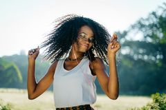 Emotional outdoor portrait. The charming young african girl with pretty smile and green eye shadows is shaking her curly Stock Image