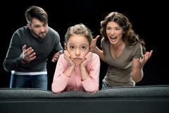 Emotional parents screaming at little daughter looking at camera. Family problems concept Royalty Free Stock Image