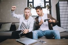 Gamers playing party. Emotional picture of two gamers playing the game. The guy on the left is winning, keeping his right hand in fist and whistling while the Stock Photography