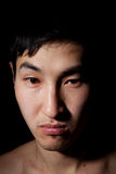 Emotional portrait. The obverse portrait of the young Asian man which frowns Stock Photos